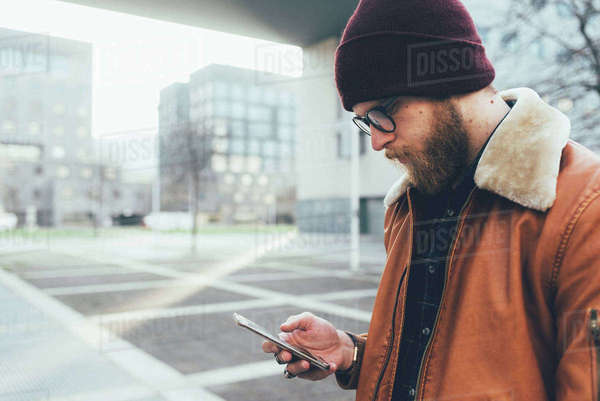 Young male hipster in city looking at smartphone Royalty-free stock photo