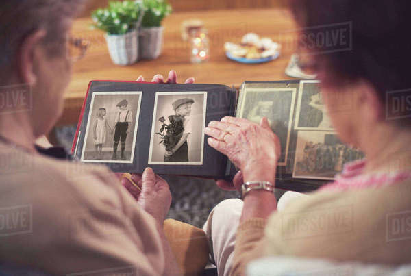 Over shoulder view of two senior women looking at old photograph album Royalty-free stock photo
