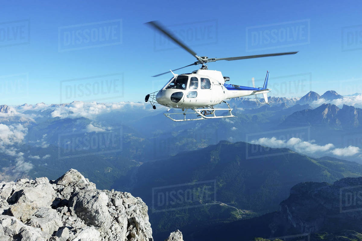 Helicopter approaching BASE jumper exit at the cliff edge stock photo