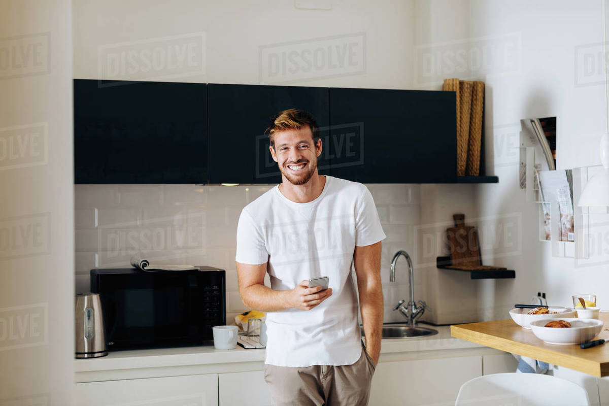 Young man using smartphone in kitchen Royalty-free stock photo