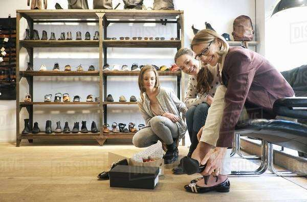 Three generation females trying out shoes in shoe shop Royalty-free stock photo