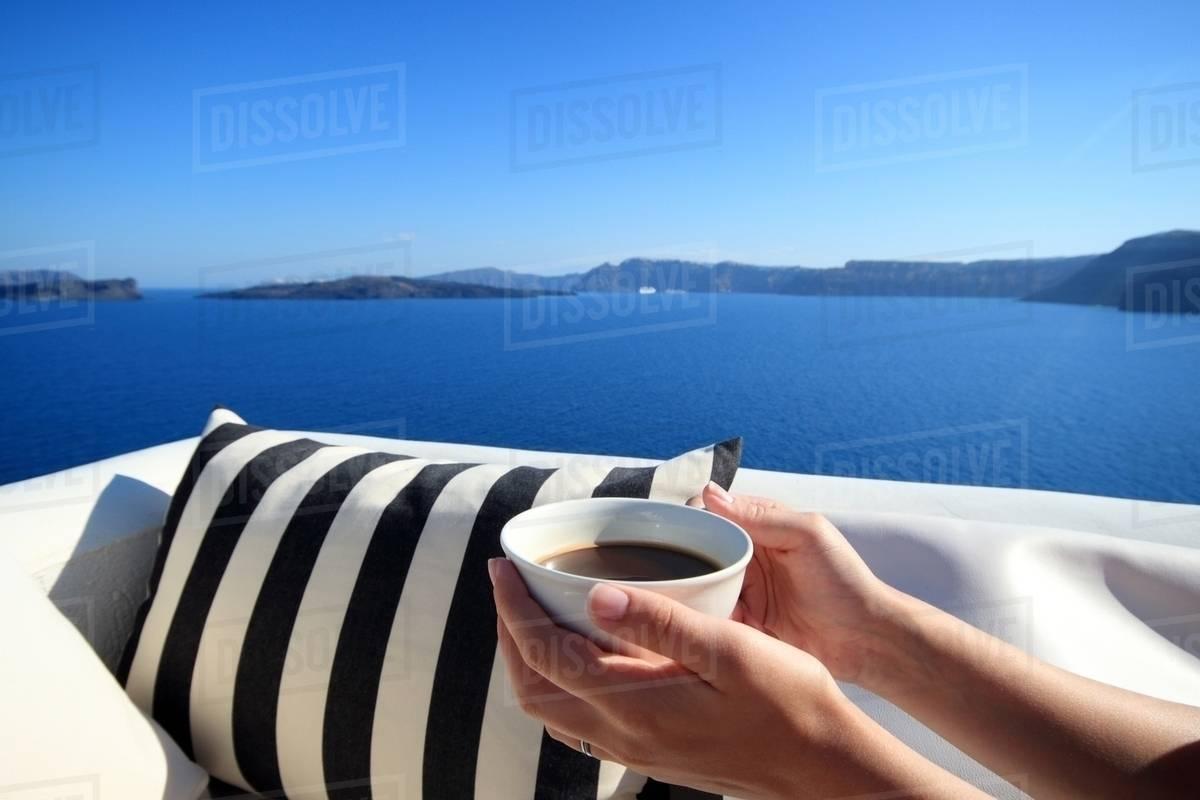 1450c5f9281 Female hands holding coffee cup on balcony, Santorini, Cyclades Islands,  Greece