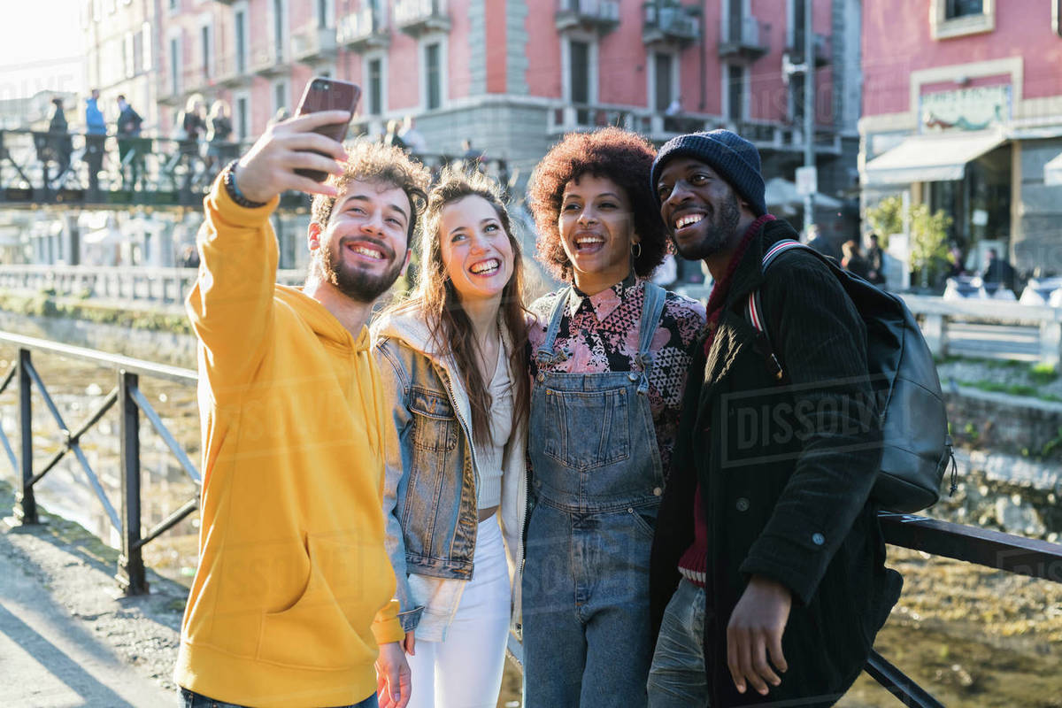Four female and male young adult friends taking selfie on city canal waterfront Royalty-free stock photo