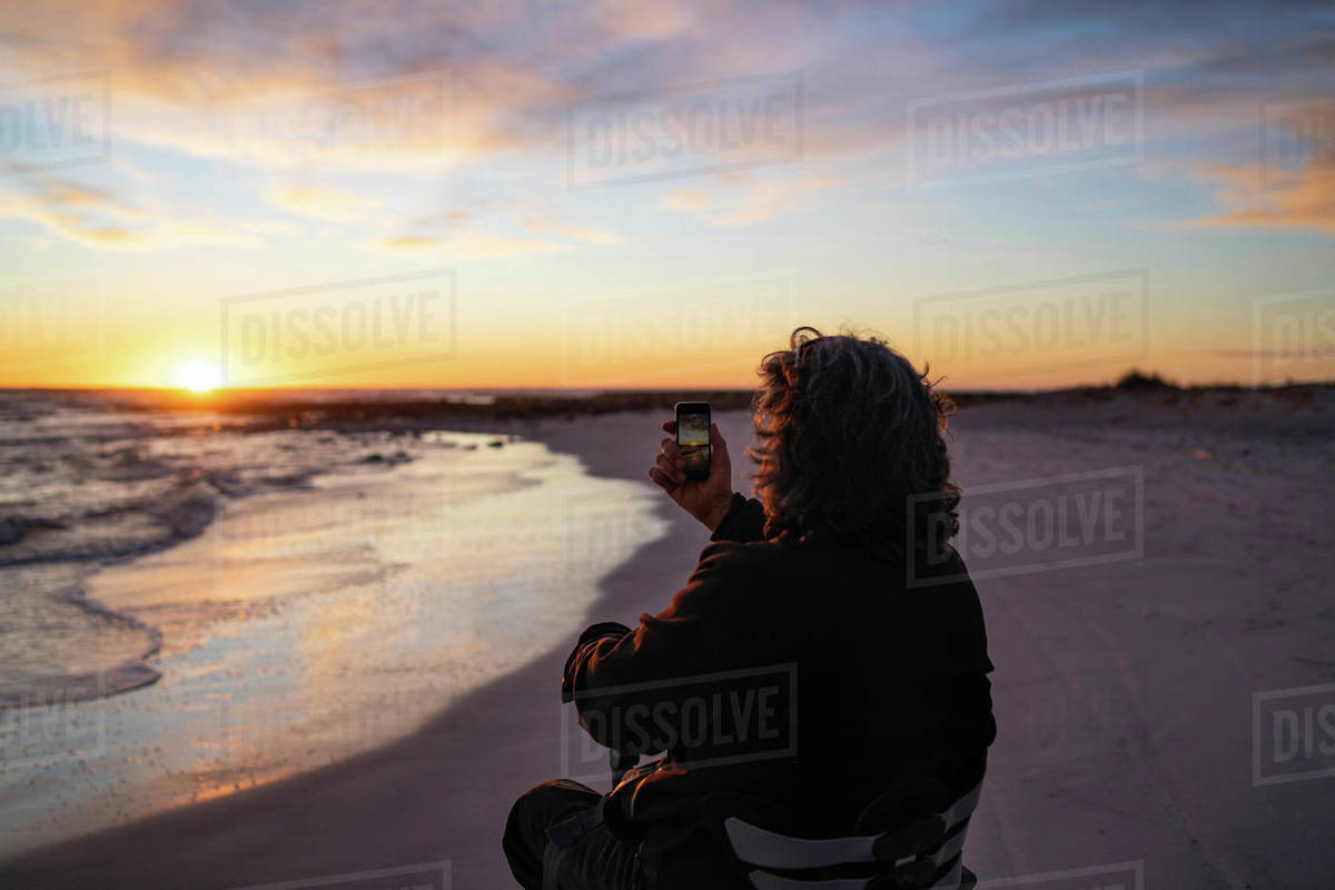 Man on wheels taking photograph of sunset with smartphone at seaside Royalty-free stock photo