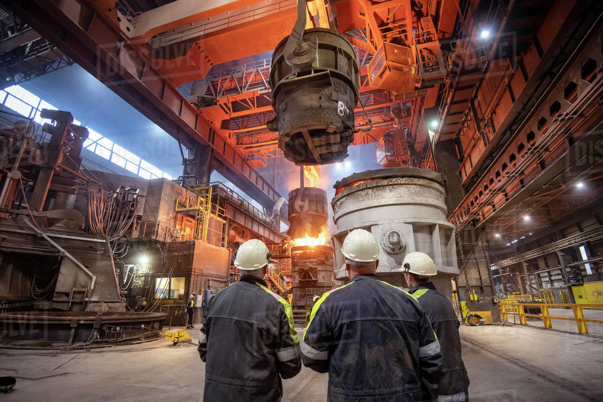 Three steelworkers watching molten steel pour in steelworks Royalty-free stock photo