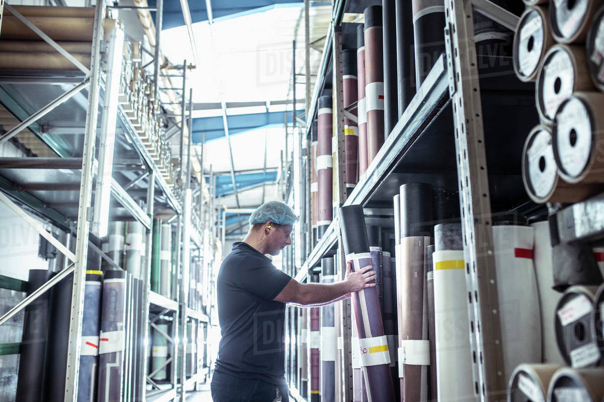 Worker selecting print rolls in print factory Royalty-free stock photo