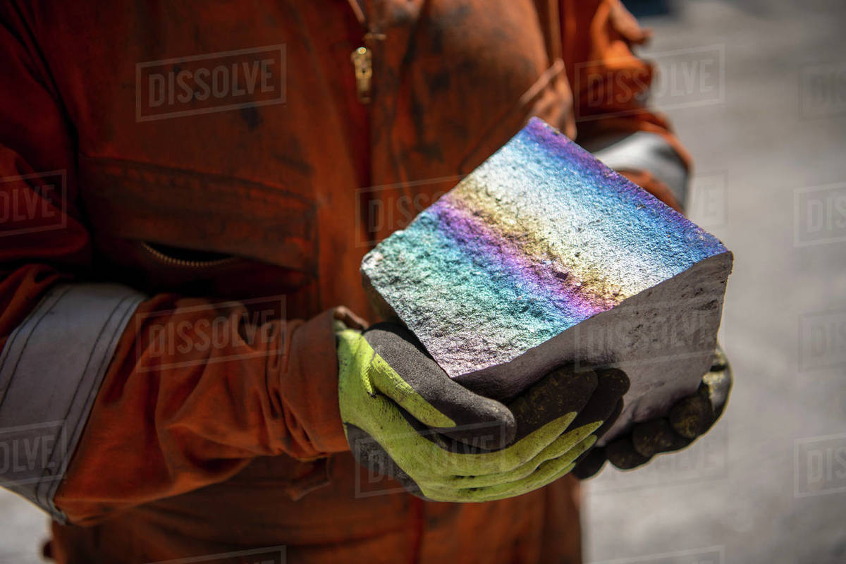 Worker holding fractured block of titanium alloy with coloured iridescence in titanium recycling plant Royalty-free stock photo