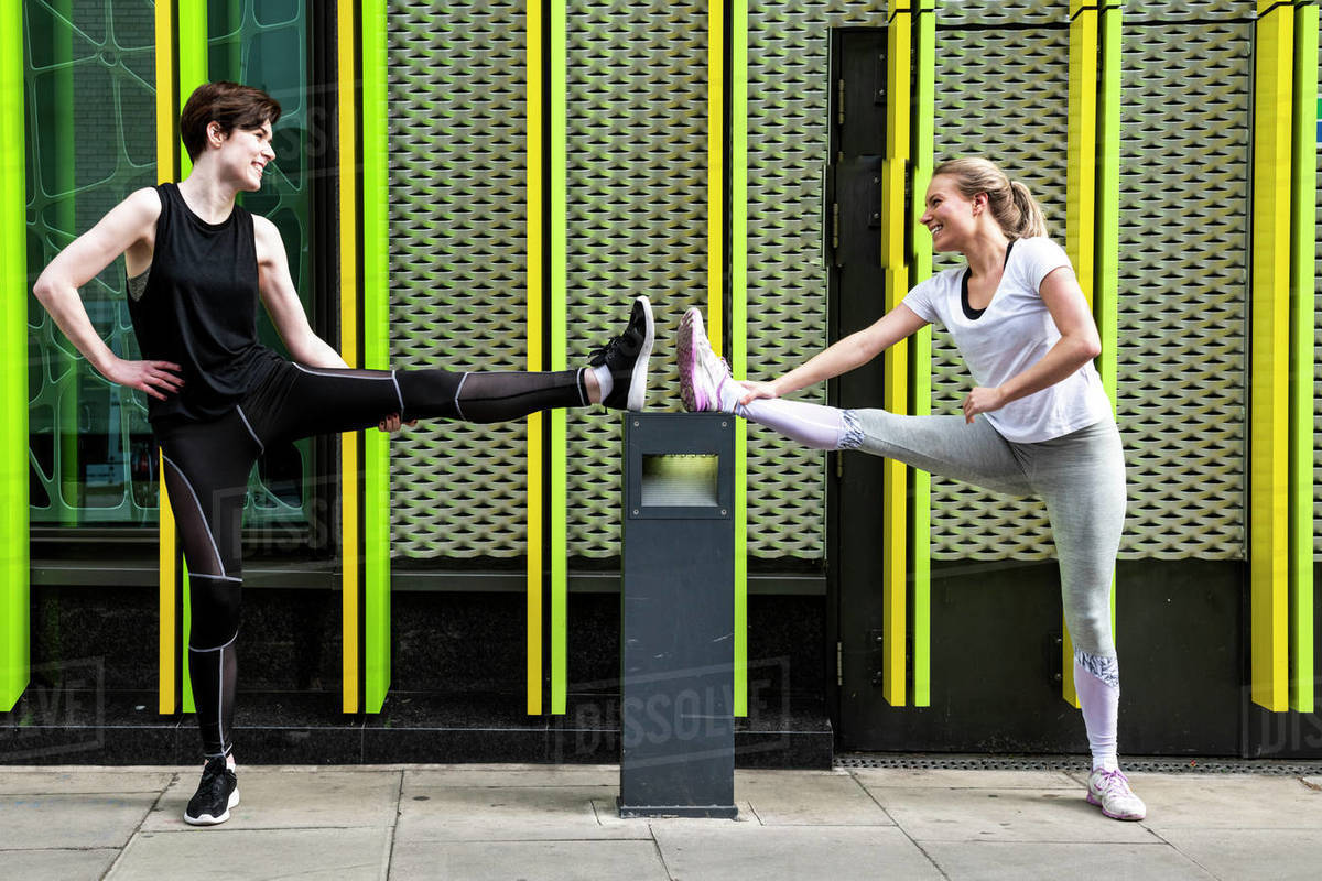 Two young female runners stretching legs on city sidewalk, full length Royalty-free stock photo