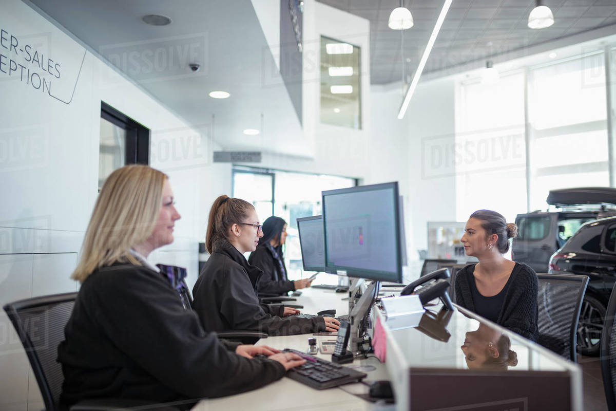 Female customer and staff at service desk in car dealership Royalty-free stock photo