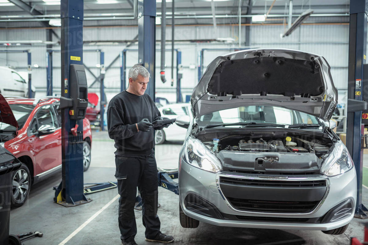 Engineer inspecting car in car service centre Royalty-free stock photo