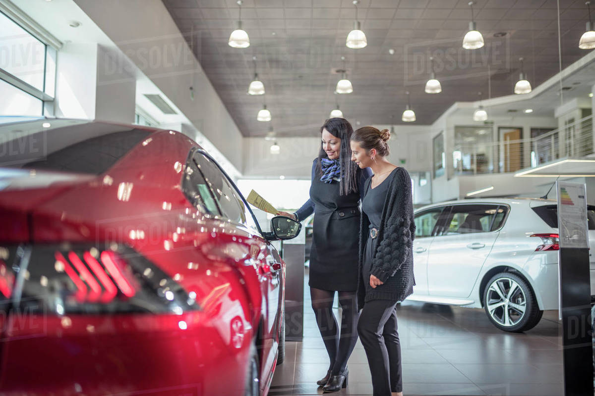 Saleswoman and customer inspecting new car in car showroom Royalty-free stock photo