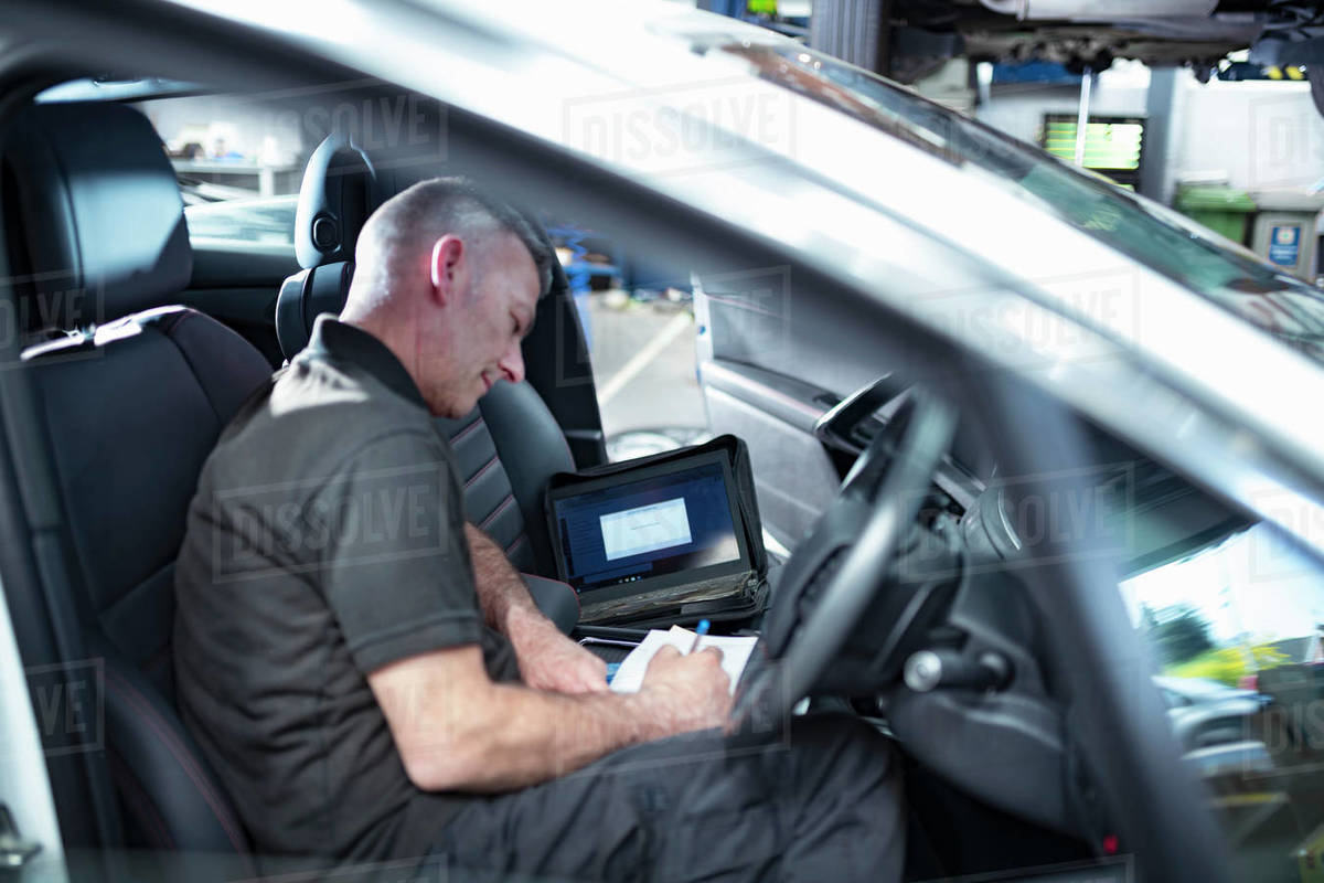 Engineer using computer to check car electronics in car service centre Royalty-free stock photo