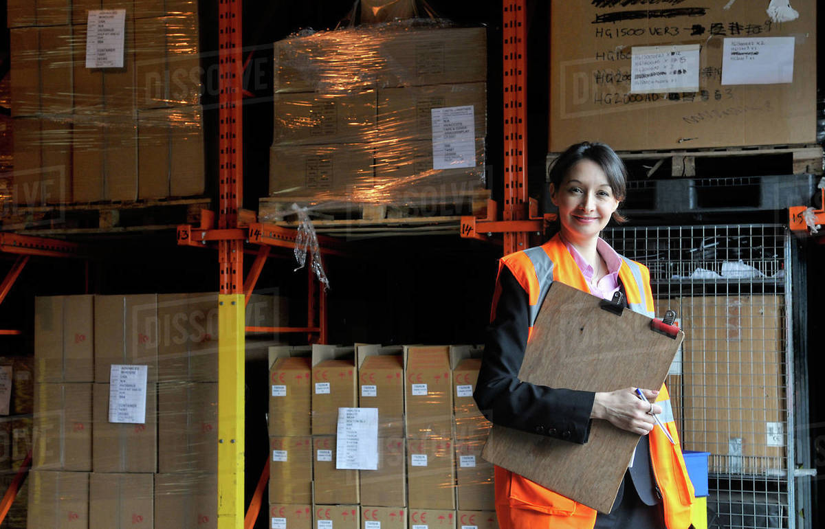 Young female factory worker with clipboard in warehouse, portrait Royalty-free stock photo