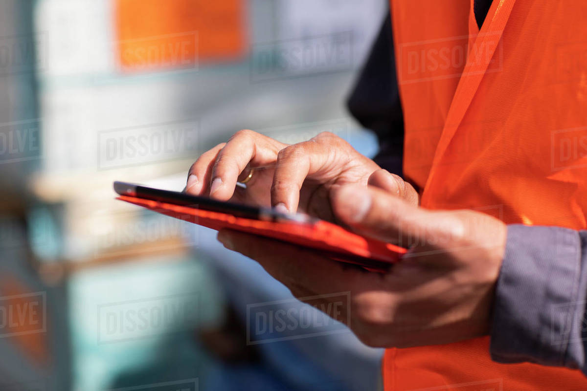 Male engineer on construction site using digital tablet touchscreen, close up of hands Royalty-free stock photo