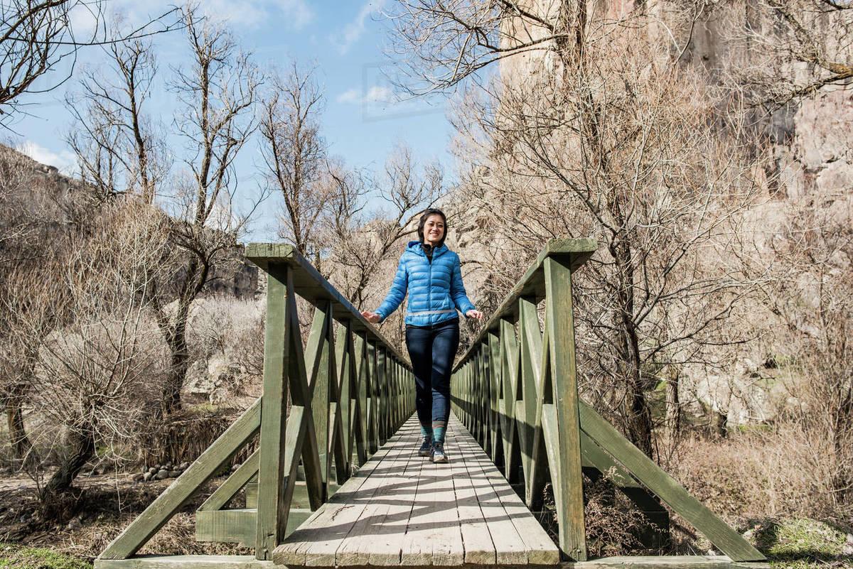 Woman crossing wooden bridge in forest, Göreme, Cappadocia, Nevsehir, Turkey Royalty-free stock photo