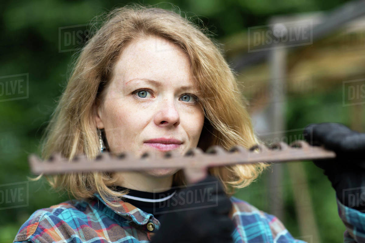 Mid adult woman holding garden rake, head and shoulder portrait Royalty-free stock photo