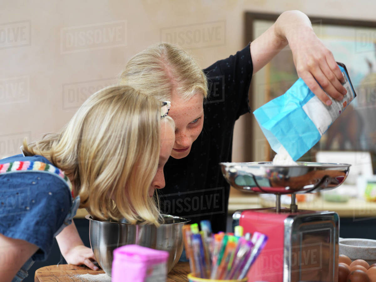 Girl and her sister baking a cake, weighing flour on kitchen scales Royalty-free stock photo