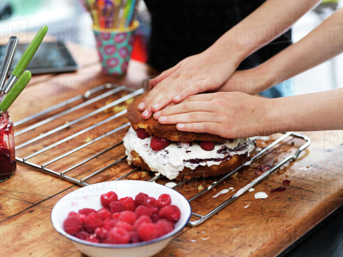 Girl and her sister baking a cake, pressing down top layer at kitchen table, cropped view of hands Royalty-free stock photo