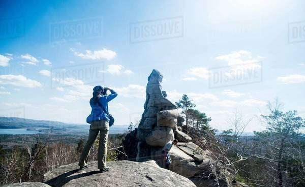 Two hikers on top of rock formation taking photographs Royalty-free stock photo