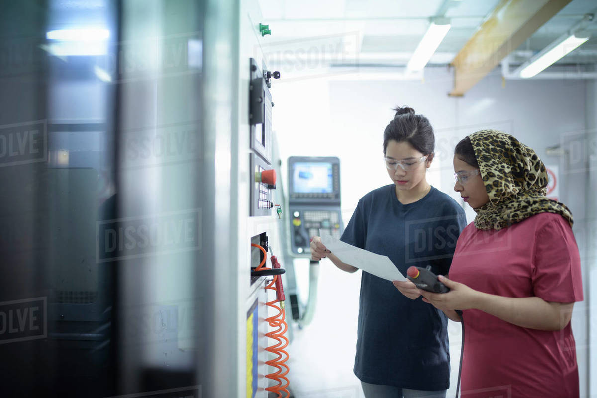 Two female engineers inspecting CNC lathe in factory. Royalty-free stock photo