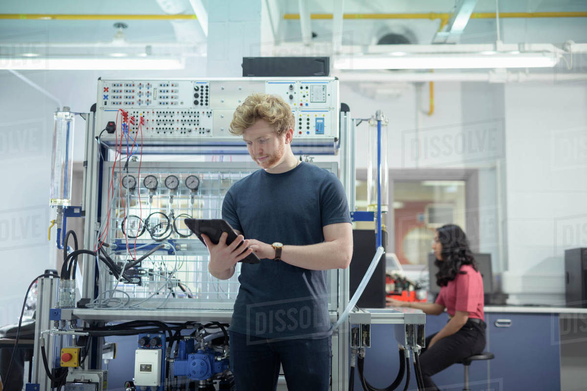 Male and female trainee engineers with experimental equipment in research facility. Royalty-free stock photo