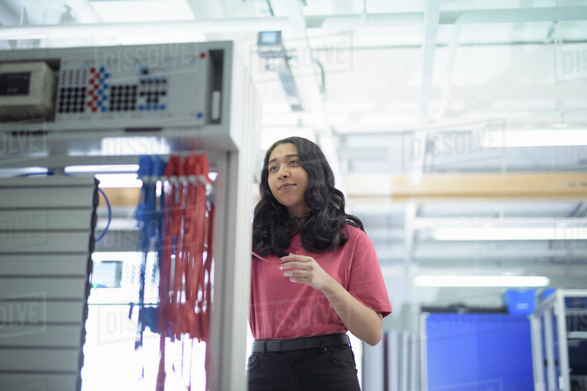 Female trainee electronics engineer standing next to test rig in research facility. Royalty-free stock photo