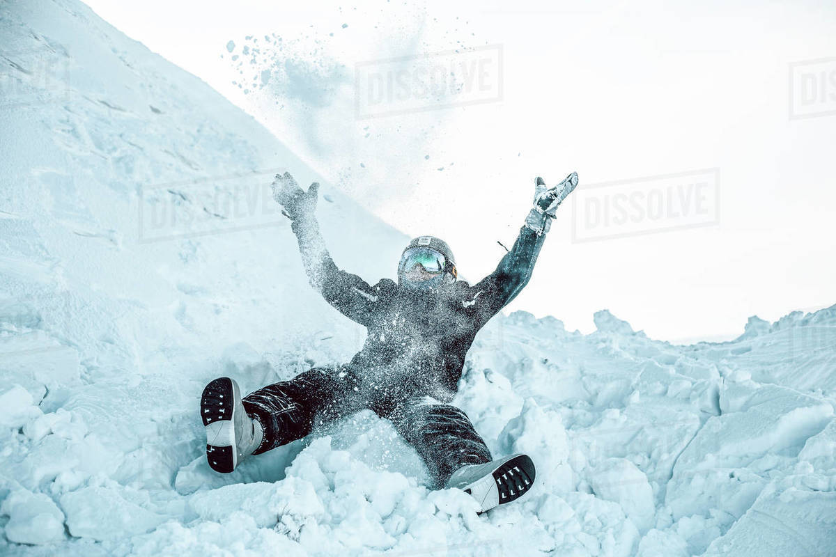 A person wearing a ski suit, helmet and goggles lying on his back in the snow.  Royalty-free stock photo