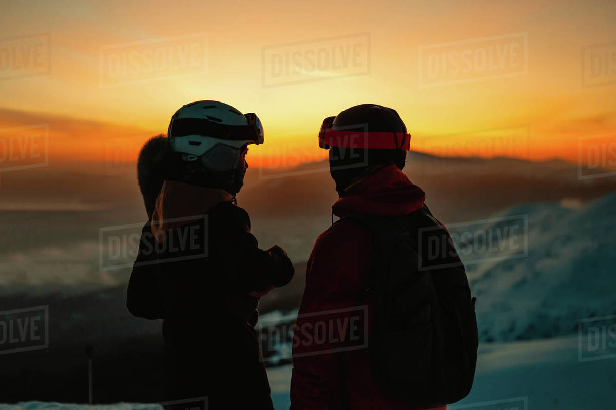 Silhouette of two people wearing ski helmets and goggles against sunset on a mountain in winter Royalty-free stock photo