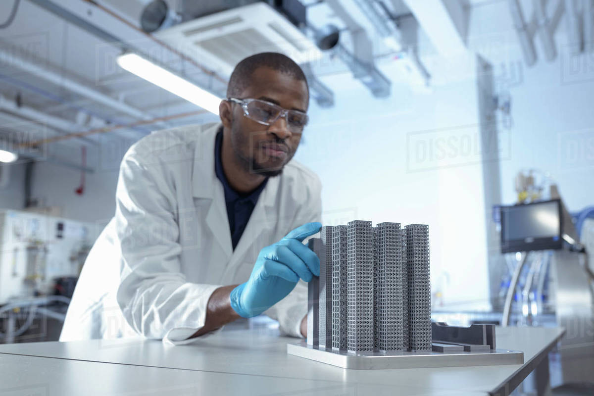 Man wearing a lab coat, eyeglasses and protective gloves leaning on a bench looking at a piece of equipment. Royalty-free stock photo