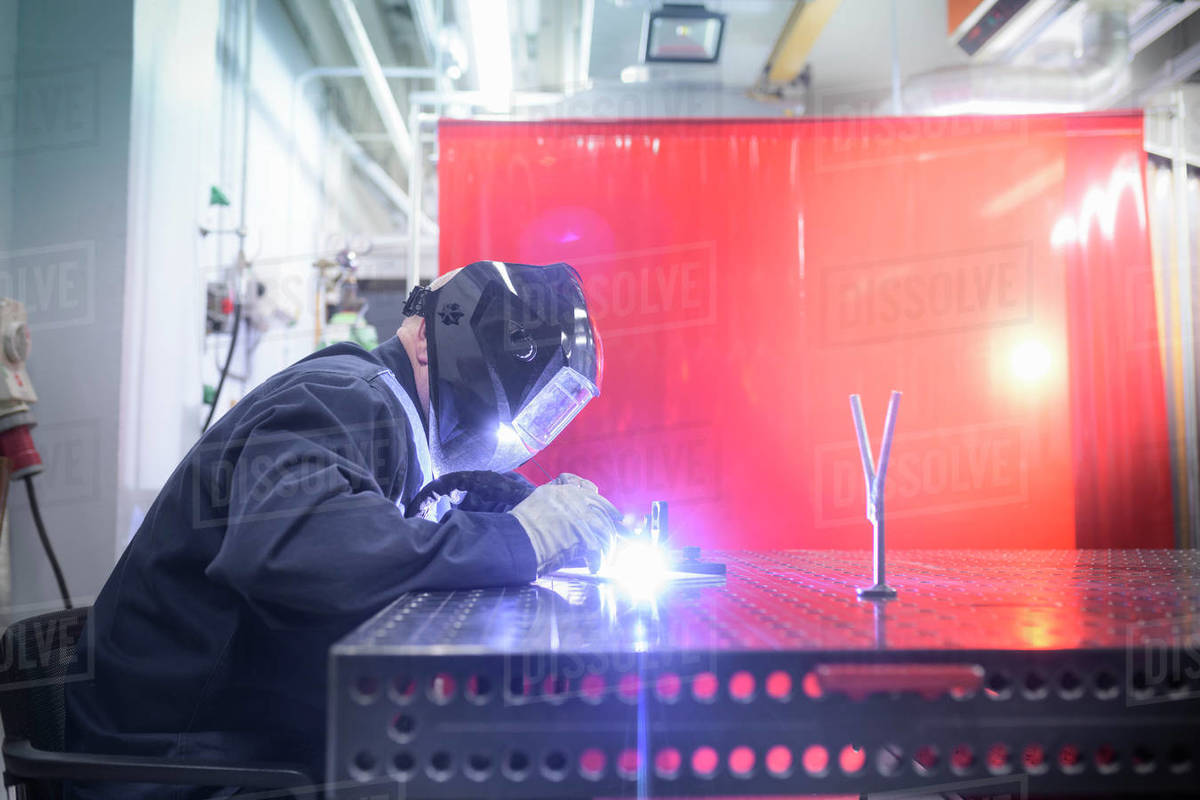 A student wearing overalls and a welding mask working at a workbench. Royalty-free stock photo