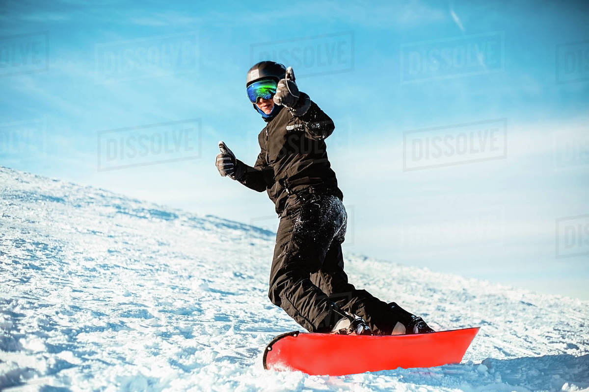 A person wearing a black ski suit, helmet and goggles skiing down a mountain on a red snowboard. Royalty-free stock photo