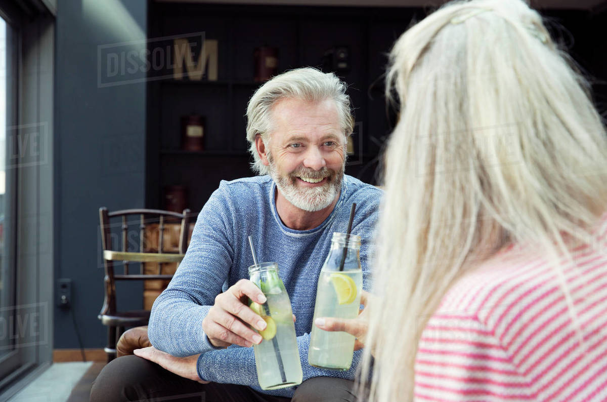 A couple clink bottles of drink sitting in a bar. Royalty-free stock photo