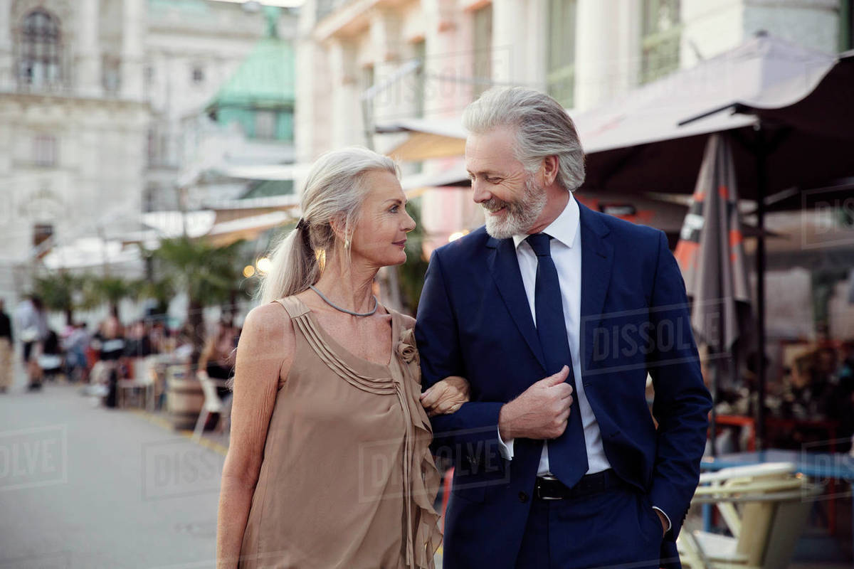 A couple walk arm in arm along a street with bars and market stalls in Vienna. Royalty-free stock photo