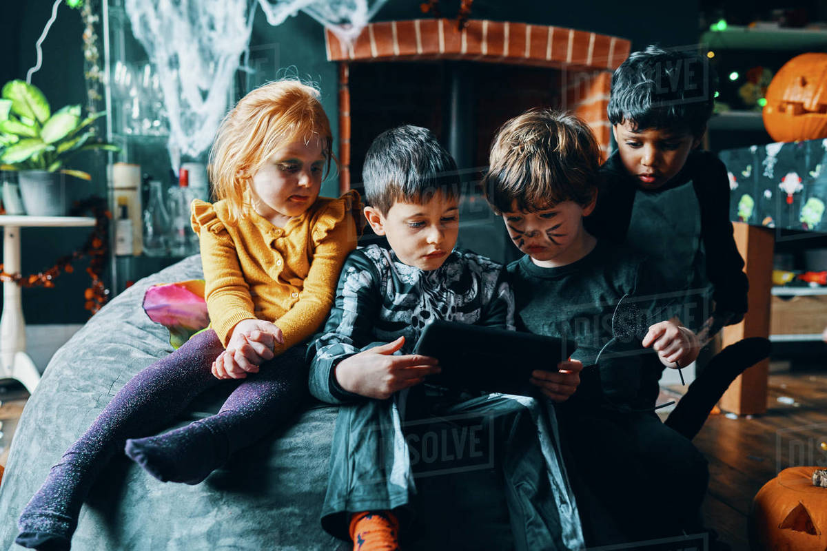 Four children sitting on a beanbag looking at a computer tablet. Royalty-free stock photo