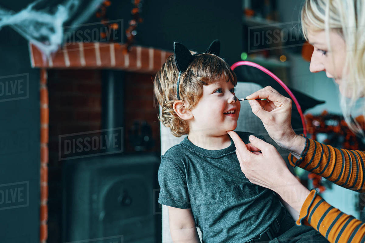 A child sitting on a chair having their face painted by a woman. Royalty-free stock photo