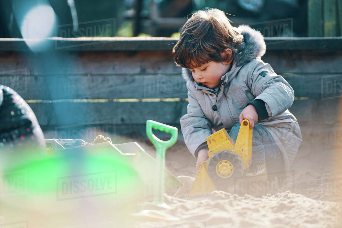 A child in a sandpit with a toy digger and spade. Royalty-free stock photo