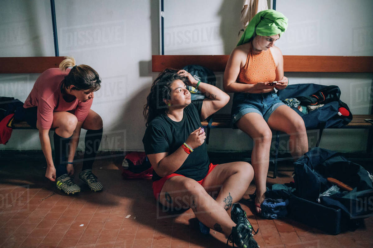 Three women sitting in the changing room after rugby training. Royalty-free stock photo