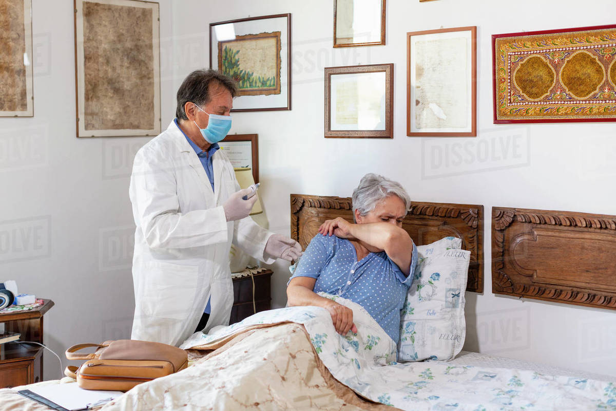A doctor making a home visit to a senior woman patient. Woman coughing covering her mouth with her arm.  Royalty-free stock photo