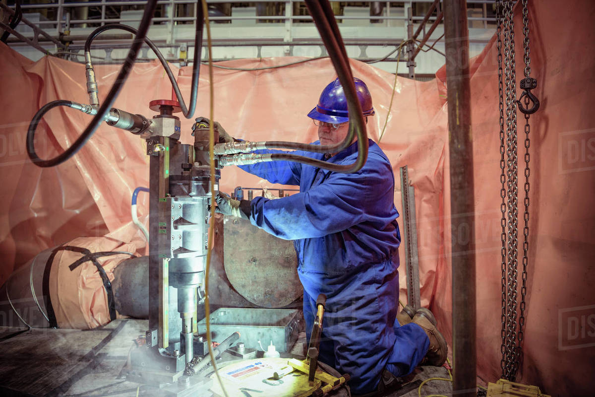 Engineer operating a drill in a  nuclear power station. Royalty-free stock photo