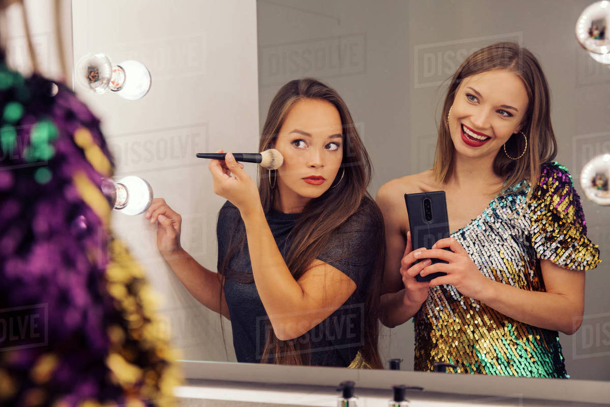 Two women putting on make up and looking in a mirror. Royalty-free stock photo