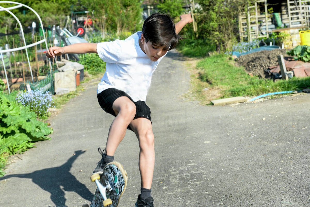 Boy with brown hair wearing t[shirt and shorts performing skateboard trick. Royalty-free stock photo