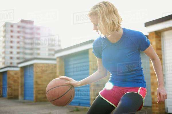 Portrait of woman bouncing basketball Royalty-free stock photo