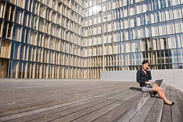 Businesswoman using laptop in front of high rise building, Paris, Île-de-France, France Royalty-free stock photo