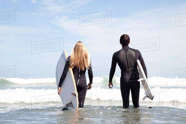 Young couple walking out to sea holding surfboards, rear view Royalty-free stock photo