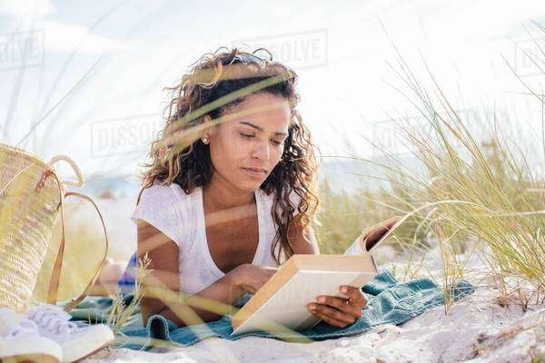 Young woman cross reading a book in beach dunes, Tuscany, Italy Royalty-free stock photo