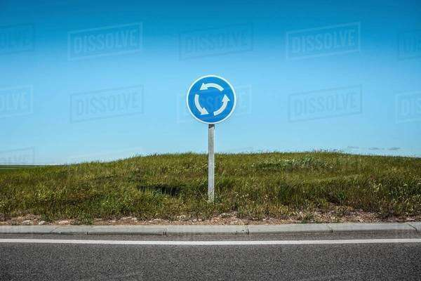 Roundabout sign by edge of road Royalty-free stock photo