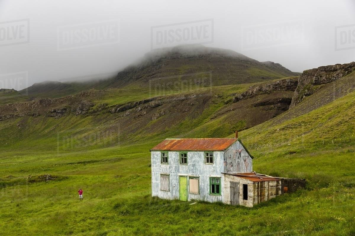 Distant view of girl playing near abandoned house, Stryta, Iceland stock  photo