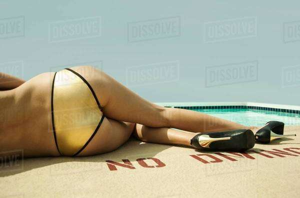 Waist down of young woman wearing gold bikini bottoms lying poolside Royalty-free stock photo
