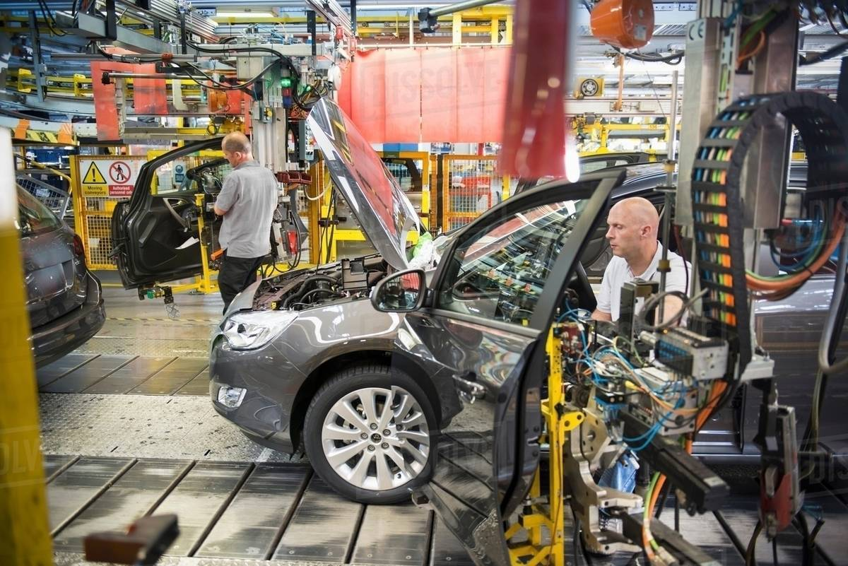 Car Embly Workers Ing Doors To Cars On Production Line In Factory