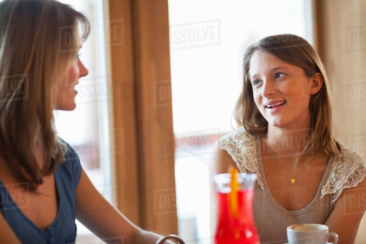a41448a21c Two young women chatting in cafe bar - Stock Photo - Dissolve